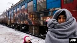 Мигрант, завернутый в одеяло, чтобы согреться ждет поезд, направляющийся с границы Хорватии на вокзале Прешево, 19 января 2016 года.