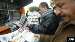 Iraq -- Kurdish men read newspapers headlines at a news stand in the northern city of Irbil, 08Mar2010