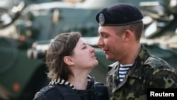 A Ukrainian marine speaks with his wife after a welcoming ceremony in Kyiv after their return from a military base in the Crimean port city of Feodosia.