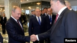 Президент Украины Пётр Порошенко (справа) и президент России Владимир Путин (слева) приветствуют друг друга. Рядом стоит президент Казахстана Нурсултан Назарбаев. Минск, 26 августа 2014 года.