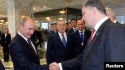 Президент Украины Петр Порошенко пожимает руку президенту России Владимиру Путину (слева) в присутствии президента Казахстана Нурсултана Назарбаева. Минск, 26 августа 2014 года.