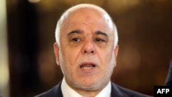Iraqi Prime Minster Haidar al-Abadi speaks to the press at the airport in Baghdad before leaving for the United States on April 13.