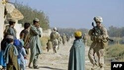 Американский пехотинец разговаривает с детьми во время патрулирования в провинции Гельменд, Афганистан, 19 ноября 2009 года