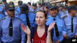 A Belarusian woman applauds in front of a police line as part of a creative antiregime protest, one of many to have taken place in the country in recent weeks.