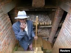 مردی در حال تمیز کردن گوری دست جمعی در رواندا