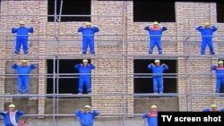 Туркменские строители делают упражнения во время Недели здоровья.