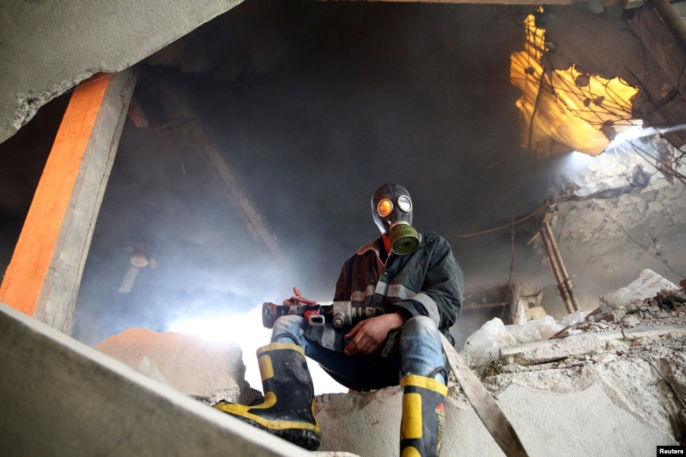 A civil-defense member sits near a site hit by an air strike in the rebel-held Douma neighborhood of Damascus, Syria. (Reuters/Bassam Khabieh)