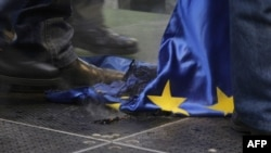 Hungarian protesters trample a burnt EU flag at a rally called by the right-wing party Jobbik in front of the EU headquarters in downtown Budapest in January 2012.