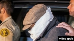 Накула Басселиді полиция қызметкерлері ұстап әкетіп барады. Калифорния штаты, АҚШ. 27 қыркүйек 2012 жыл.
