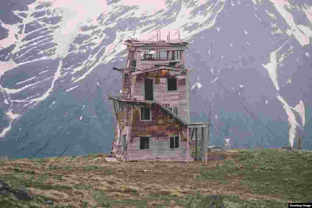 Метеостанция на Эльбрусе, Кабардино-Балкария. Она расположена на склоне Эльбруса, примерно в 200 метрах от другой известной в той местности постройки – «Терксольской обсерватории». Предположительно, метеостанция работала до 1980-х годов. По словам блогеров, они были там дважды. В последний раз– два года назад. Внутри остались деревянные полы и разрушенная печь. Существует также лестница, по которой можно подняться на третий этаж. Это место стало перевальным пунктом у альпинистов. Здесь они акклиматизируются перед подъемом в высокогорья