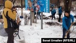«Жас эколог» жастар ұйымының мүшесін (оң жақта) журналистер суретке түсіріп тұр. Орал, 21 қараша 2015 жыл.