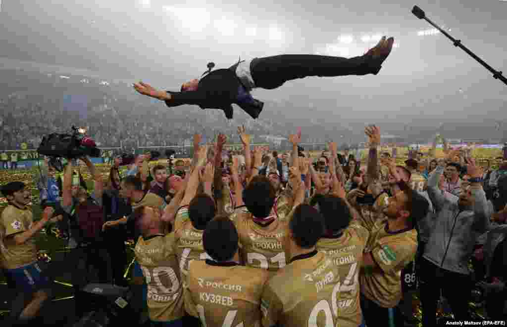 Soccer players from FC Zenit St. Petersburg throw their head coach Sergei Semak into the air to celebrate winning the Russian Premier League title on May 12. (epa-EFE/Anatoly Maltsev)