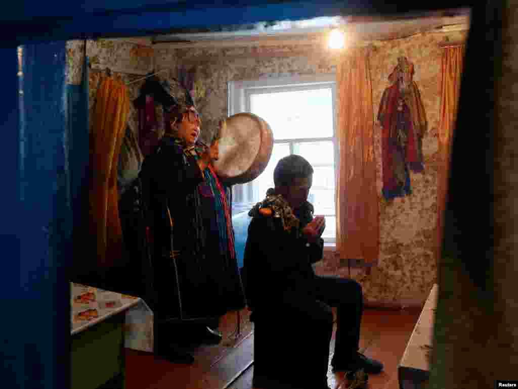"""По поверьям тувинцев, обычные люди не могут стать шаманами по собственному желанию. Кто именно будет шаманом – решает дух, который вселяется в тело человека. На фото: Анисия Монгуш из общества """"Дунгур"""" (бубен) изгоняет злых духов во время спиритического сеанса."""