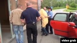 Швед полицияси Нодира Аминовани суд биносига олиб кирмоқда.