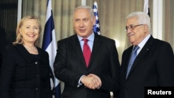 Israeli Prime Minister Binyamin Netanyahu (center) shakes hands with Palestinian Authority President Mahmud Abbas (right) as U.S. Secretary of State Hillary Clinton looks on at Netanyahu's residence in Jerusalem last month.