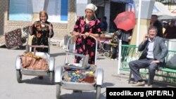 Женщины идут с рынка в городе Гиждувон, Узбекистан.
