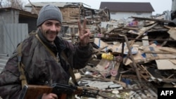 A pro-Russian gunman gestures in front of damaged houses on the outskirts of Donetsk.