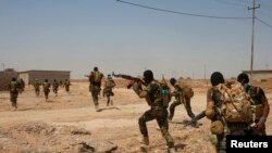Shi'ite fighters of the Asaib Ahl al-Haqq brigade prepare for an assault on an IS-held village in northwestern Iraq in September 2014.