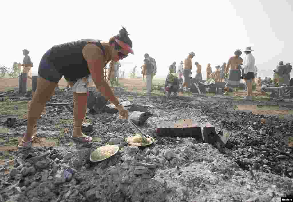 "Rhonda Clark cooks breakfast on the burned remains of the ""man"" during the Burning Man 2013 arts and music festival in the Black Rock Desert of Nevada."