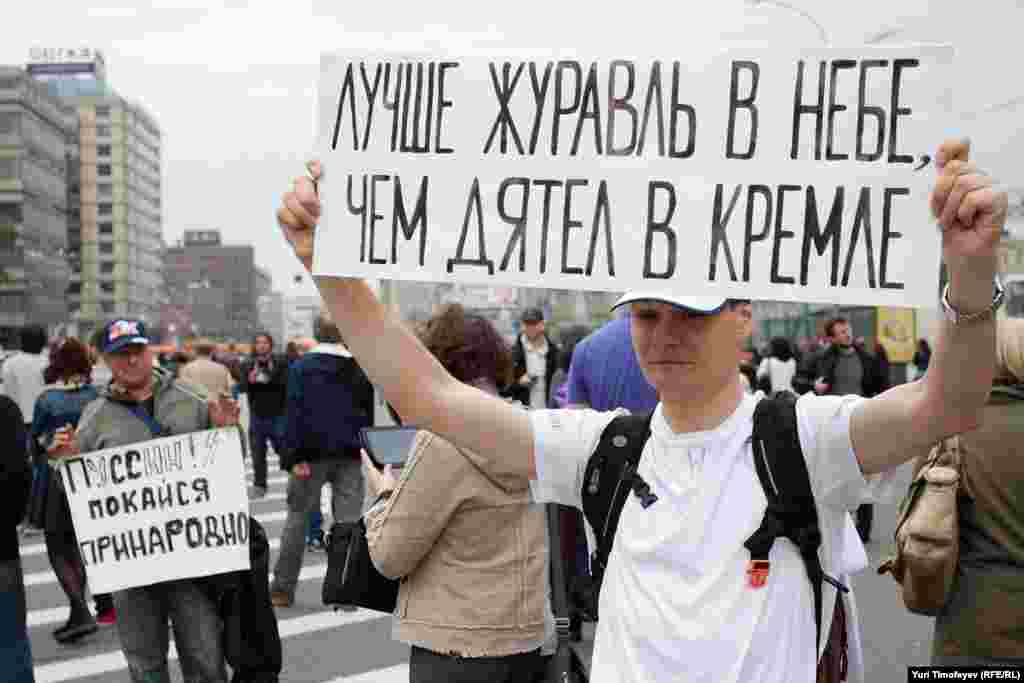 "In another vulgar Russian reference, this man holds up a sign that says: ""A crane in the sky is better than a woodpecker in the Kremlin."""