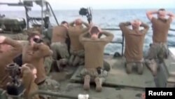 U.S. sailors are pictured on a boat with their hands on their heads at an unknown location in this still image taken from video taken on January 12-13.