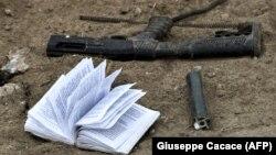 Брошенная кем-то на поле боя книга на русском и арабском языках вблизи фрагментов оружия.