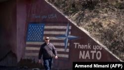 """Një person kalon pran një grafiti ku shkruan """"Faleminderit SHBA"""" dhe """"Faleminderit NATO""""."""