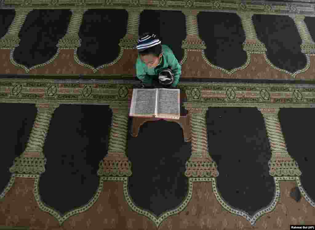 An Afghan boy reads from the Koran during the Muslim holy month of Ramadan at a mosque in Kabul. (AP/Rahmat Gul)