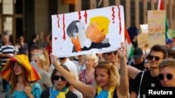 A woman wearing the colors of the Ukrainian flag takes part in a protest rally in Helsinki on July 15, one day before a planned meeting between U.S. President Donald Trump and Russian President Vladimir Putin in the Finnish capital.