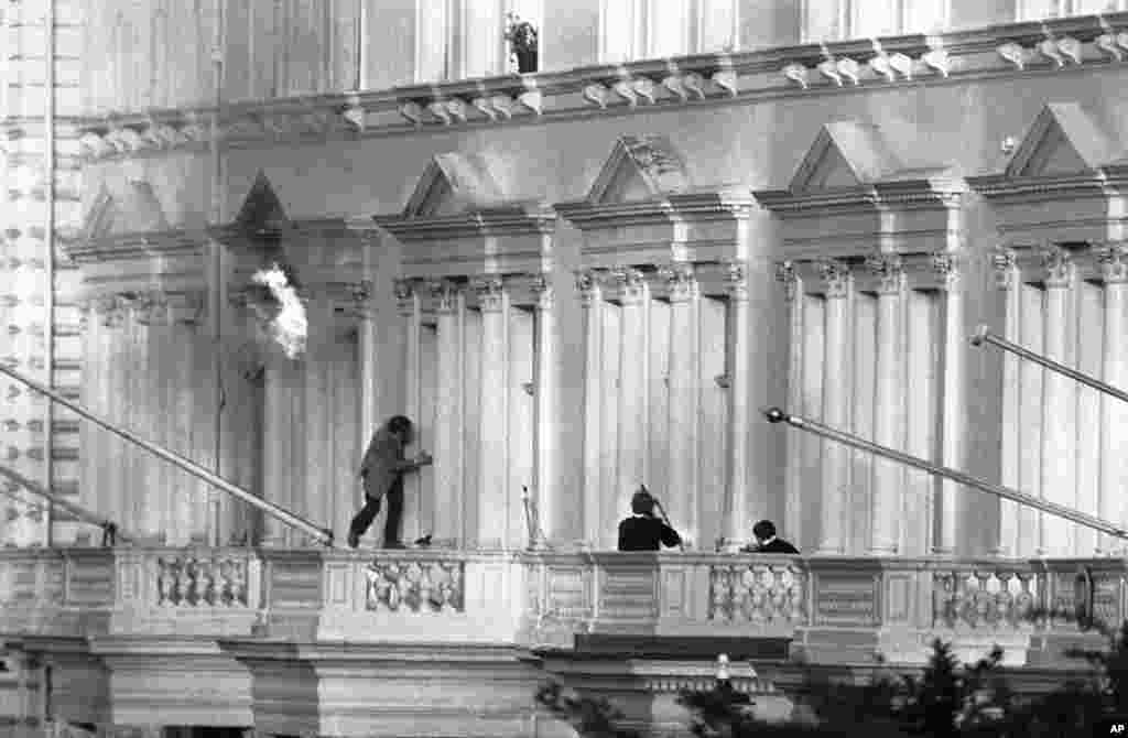 "One of the hostages, BBC sound recordist Sim Harris, climbs along the balcony following two explosions. His escape was watched by millions on live television. ""They were throwing in grenades and the room was burning, so I had to crawl out onto the balcony and I was ready to jump actually. I thought, well, if I could get out of this with a broken leg I would be all right,"" Harris told the BBC. Harris went to the embassy on April 30 with his colleague, BBC journalist Chris Kramer, over visa issues."