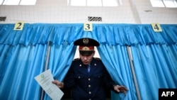 Kzakhstan -- A Kazakh policeman votes during parliamentary elections in the Kazakh city of Baikonur, also known as Russian-leased Baikonur cosmodrom, March 20, 2016