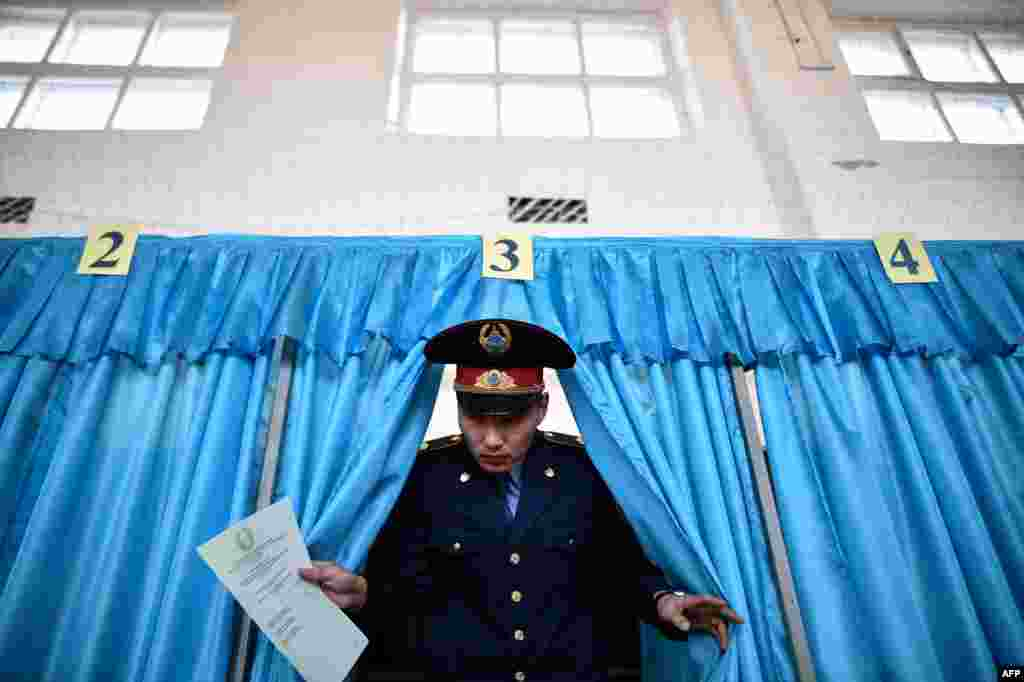 A Kazakh policeman votes during parliamentary elections in the Kazakh city of Baikonur on March 20. (AFP/Kirill Kudryavtsev)