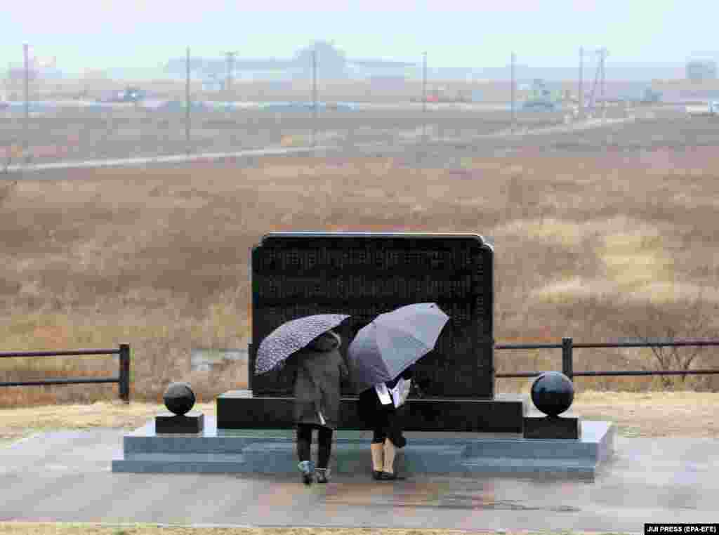 Люди моляться біля символічної могили-кенотафу за жертв землетрусу й цунамі в день восьмих роковин трагедії. Місто Наміе, 11 березня 2019 року