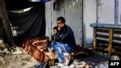 Мігрант сидить із сином перед шатром у таборі на острові Лесбос в Греції (фото архівне)
