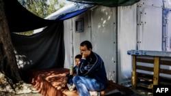 Архивска фотографија - Мигранти седнат пред монтажна куќа во бегалски камп на грчкиот остров Лезбос, 6 октомври 2016.