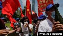 Չինաստանի կենտրոնական իշխանությունների կողմնակիցներըերկրի պետական դրոշներով ու շամպայնով նշում ենօրենքի ընդունումը, 30 հունիսի, 2020թ.