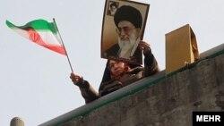 Женщина с иранским флагом и портретом аятоллы. Иллюстративное фото.