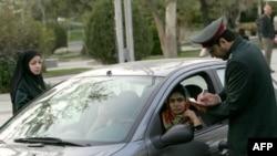 İran polisi Tehranda maşın sürən qadının sənədlərini yoxlayır.