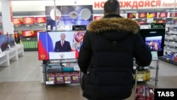 Мужчина в магазине электроники смотрит на телеэкран, по которому транслируется выступление президента России Владимира Путина. Москва, 1 декабря 2016 года.
