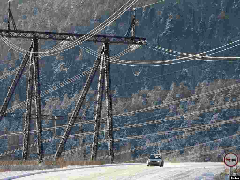 A car drives under high-voltage power lines from Krasnoyarsk hydroelectric power station, some 48 kilometers south of the Siberian city of Krasnoyarsk, on November 11. Photo by Ilya Naymushin for Reuters