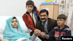 Malala Yousafzai is seen with her father Ziauddin and her two younger brothers, Khushal Khan and Atal Khan (right), as she recuperates at the Queen Elizabeth Hospital in Birmingham on October 26.
