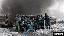 Полицейлер өртенген көлік алдында суретке түсіп тұр. Киев, 22 қаңтар 2014 жыл.