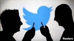 """Twitter"" sosial ulgamynyň logotipiniň öňünde telefonlary bilen hat alyşýan iki adam"