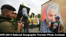 Supporters of the Hashed al-Shaabi paramilitary force and Iraq's Hezbollah brigades pose for a picture next to a poster of Iranian military commander Qassem Soleimani. January 4, 2020