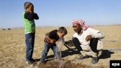 Сирия качкындары Түркия менен чектеш жерде суу ичүүдө. 26-сентябрь, 2014-жыл.