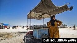 زن سوری آواره در کنار گاری خود