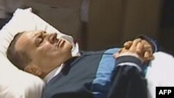 Egypt -- A TV grab shows former president Hosni Mubarak lying on a stretcher as he is wheeled into a courtroom in Cairo, 07Sep2011