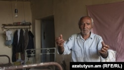 Sokrat Arakelian shows his damaged house in the village of Varhavar, which was hit by the aftershocks.