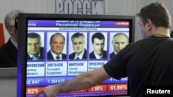 Russia -- A man gestures near a screen, which shows the preliminary results of the presidential elections, at the Central Election Commission headquarters in Moscow, 04Mar2012