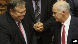 Greek Prime Minister George Papandreou (right) is congratulated by Finance Minister Evangelos Venizelos in Athens.